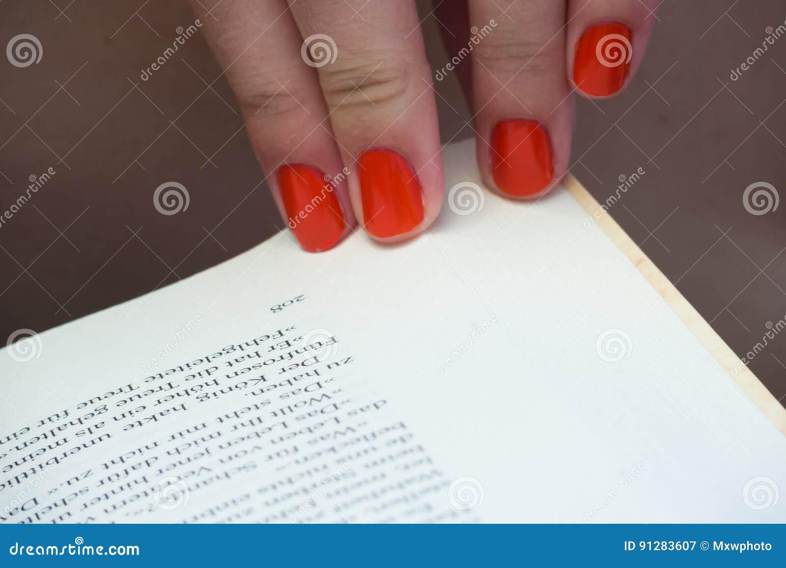 Ändrande sida av boken med orange fingernaglar