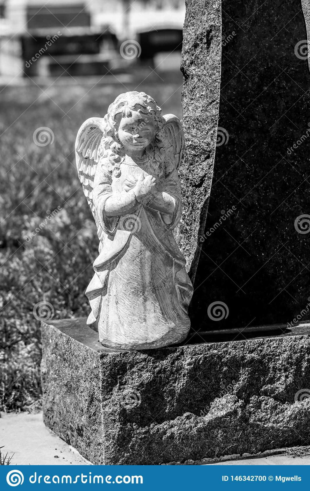Ängelstaty på sidan av gravstenen