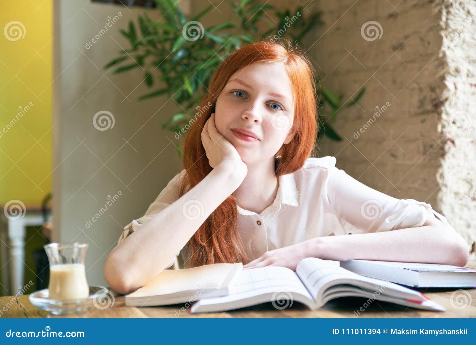 Är den kvinnliga studenten för den unga attraktiva flickan med vit hud och långt rött hår läseböcker och att studera som omger av