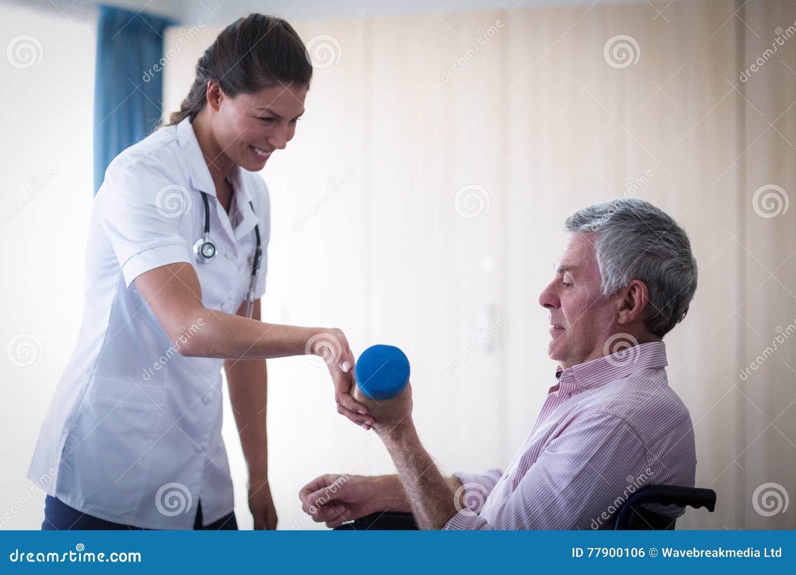 Ärztin, die älteren Mann in anhebendem Dummkopf unterstützt