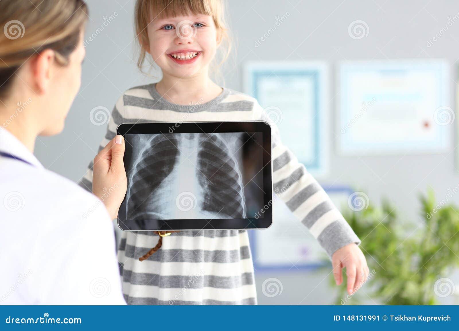Ärztin, die wenig Mädchen mit ultra modernem Überprüfungstabletten-PC-Gerät überprüft