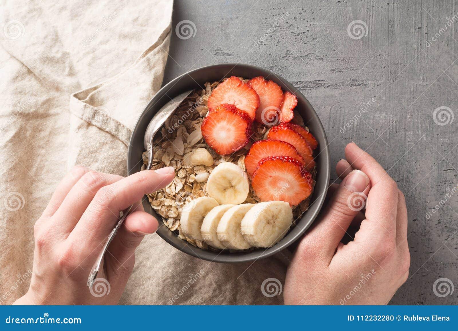 Äta den sunda frukostbunken Mysli och nya frukter i keramisk bunke i händer för kvinna` s Rent äta och att banta, detox, vegetari
