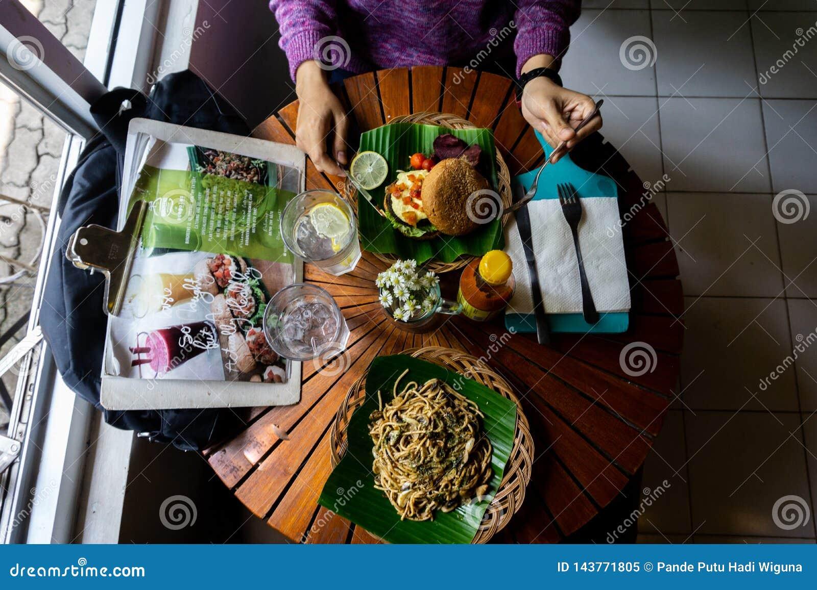 Äta en organisk sund mat på den trärunda tabellen Det finns spagetti med svartpeppar som tjänar som på det gröna bananbladet