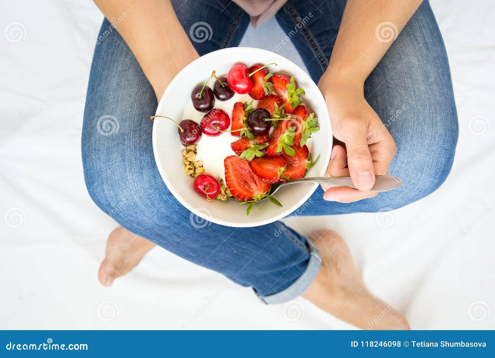 äta för begrepp som är sunt Kvinna` s räcker innehavbunken med mysli, yoghurt, jordgubben och körsbäret Top beskådar livsstil