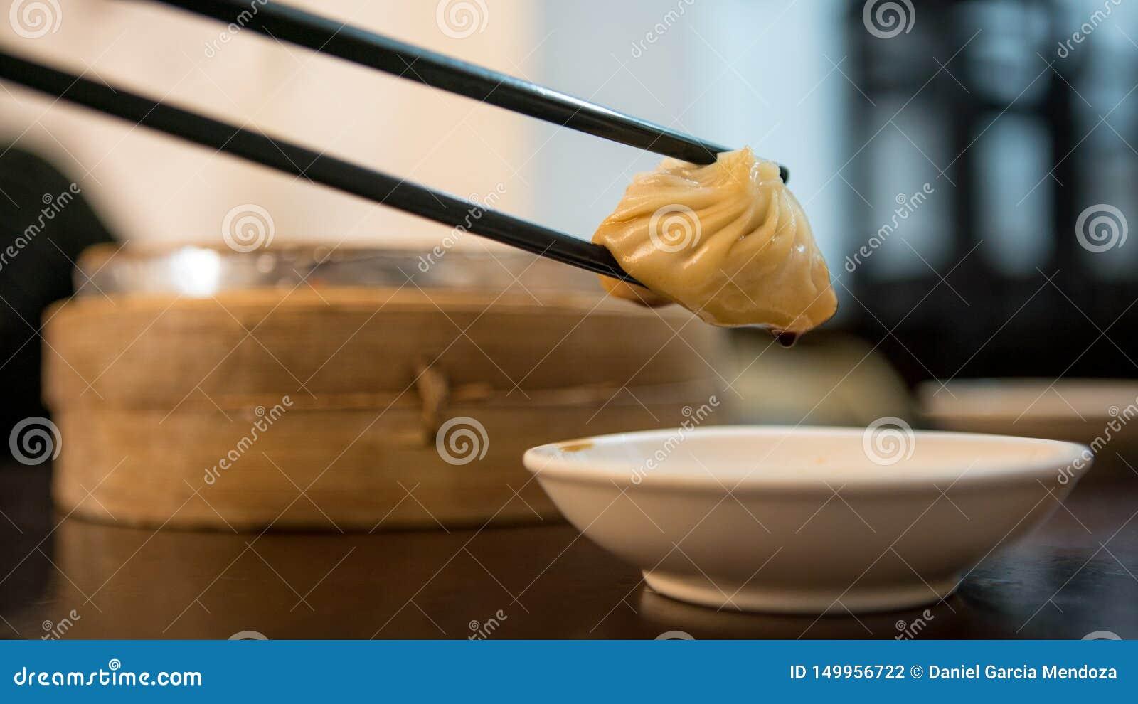 Äta klimpar i en asiatisk restaurang Traditionell kinesisk mat