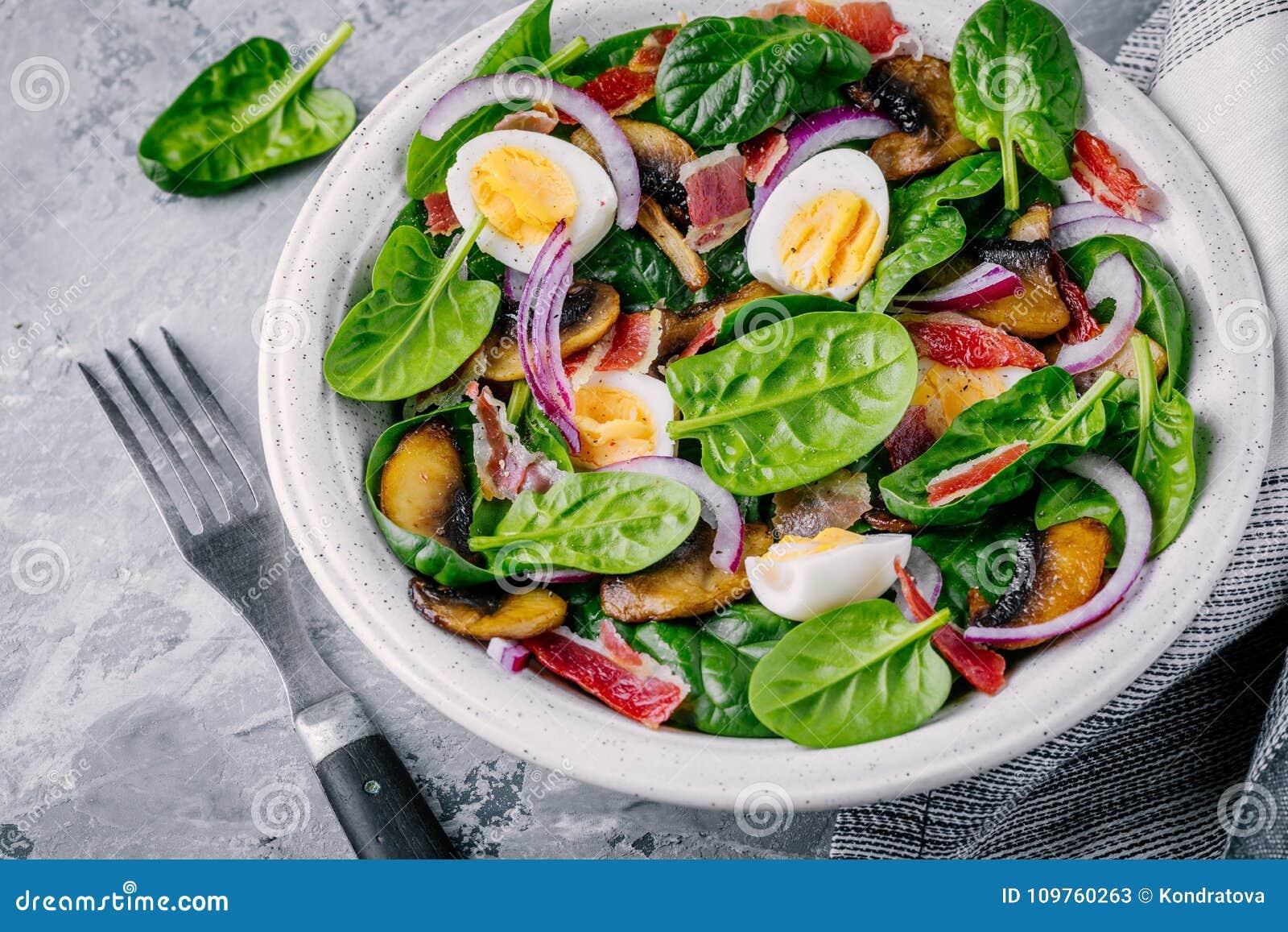 Äta lunch bunken av spenatsallad med bacon, champinjoner, ägg och röda lökar