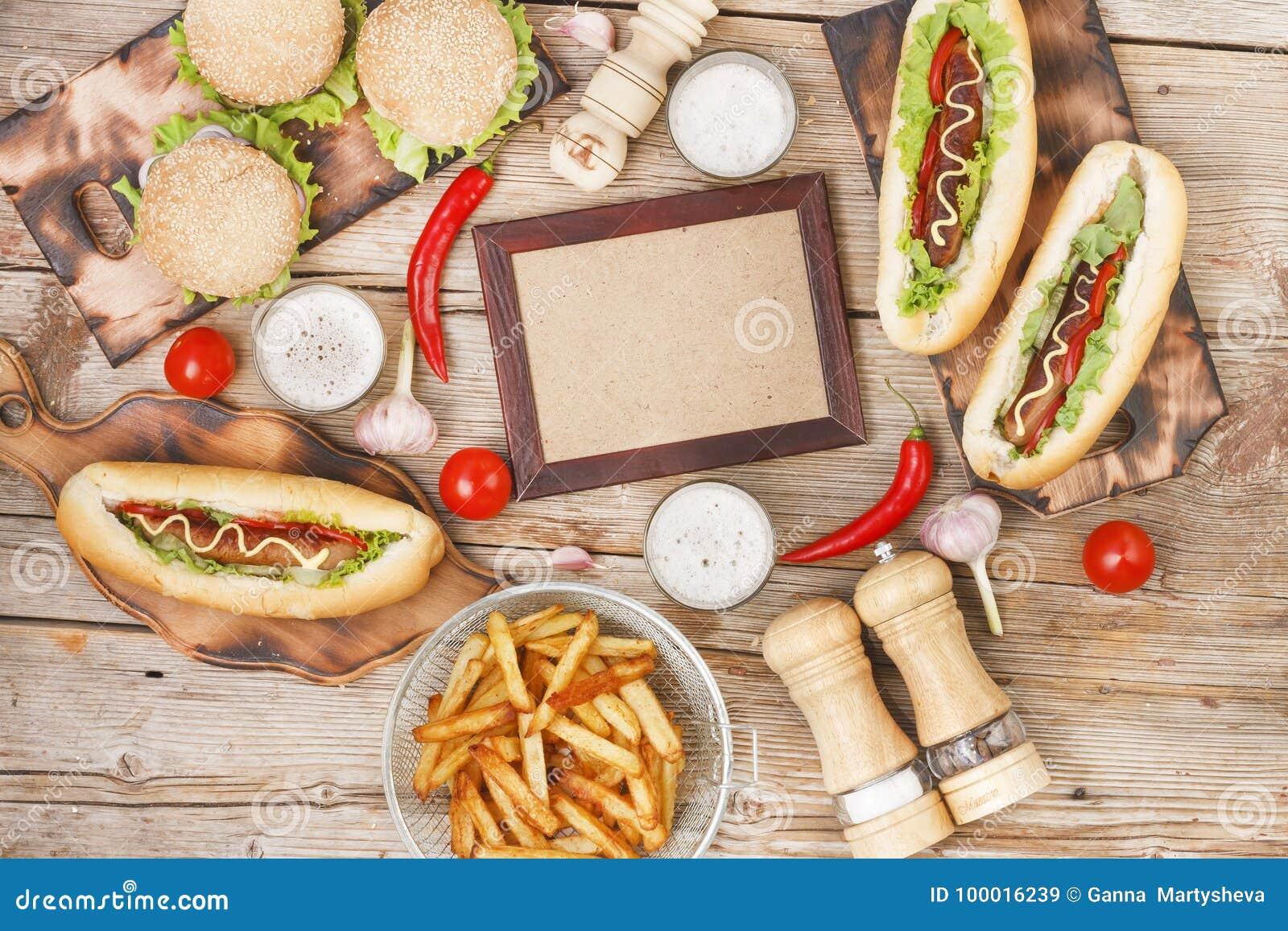 Äta middag tabellen på varmkorvdagen med kopieringsutrymme Snabbmat hotdogs, chiper, pommes frites, hantverköl,