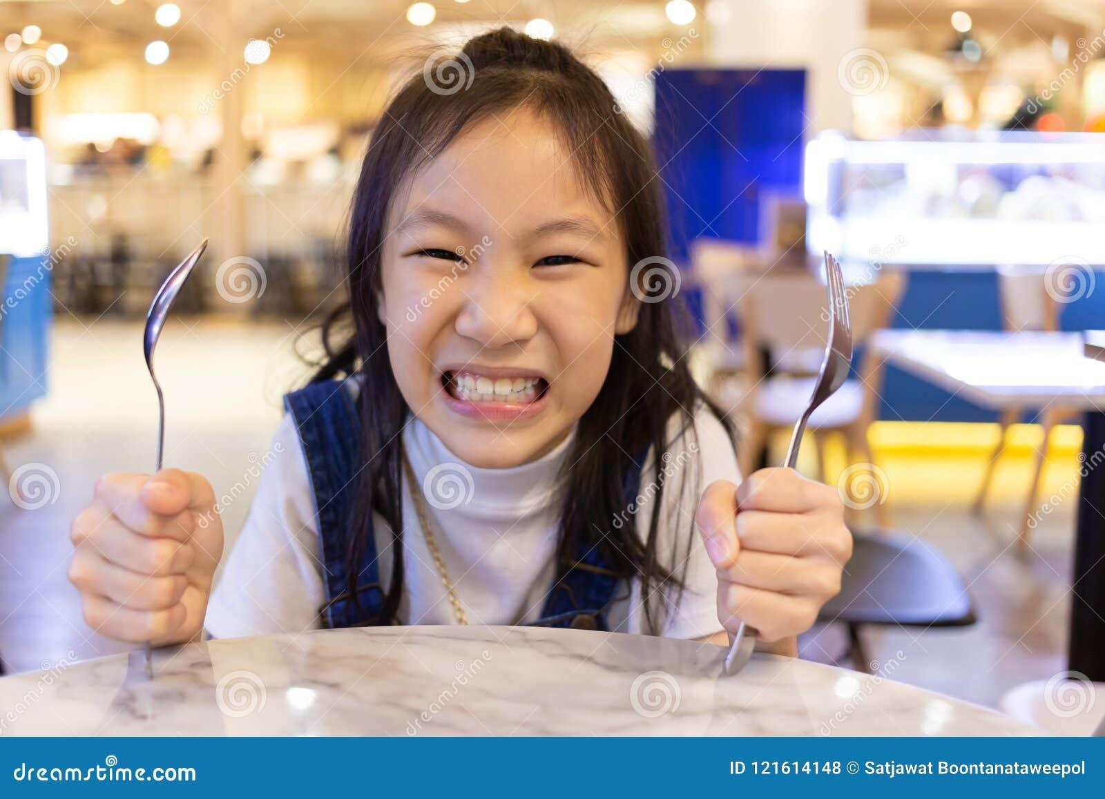 Äta oordning, lunch och ord för asiatisk gullig flicka hungrig väntande på