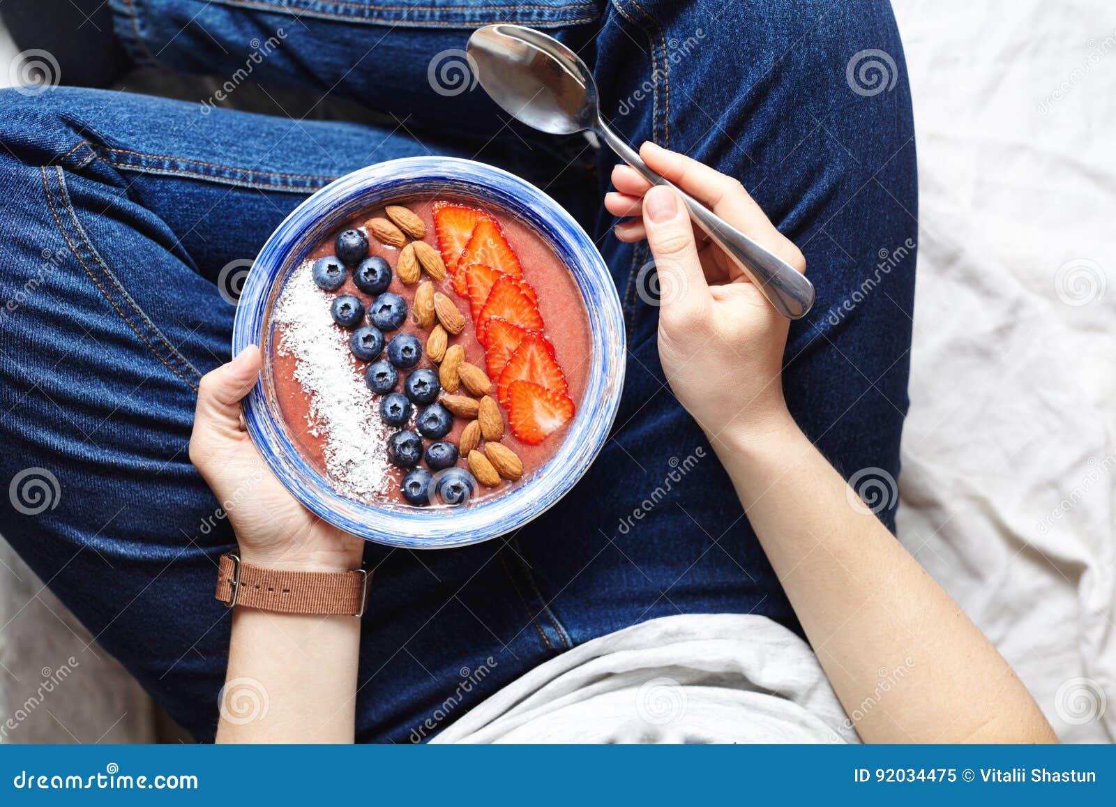 Äta smoothiesfrukostbunken För kokosnöt, nya och torra frukter för yoghurt, för jordgubbe, för blåbär, för frö, i blått keramiskt