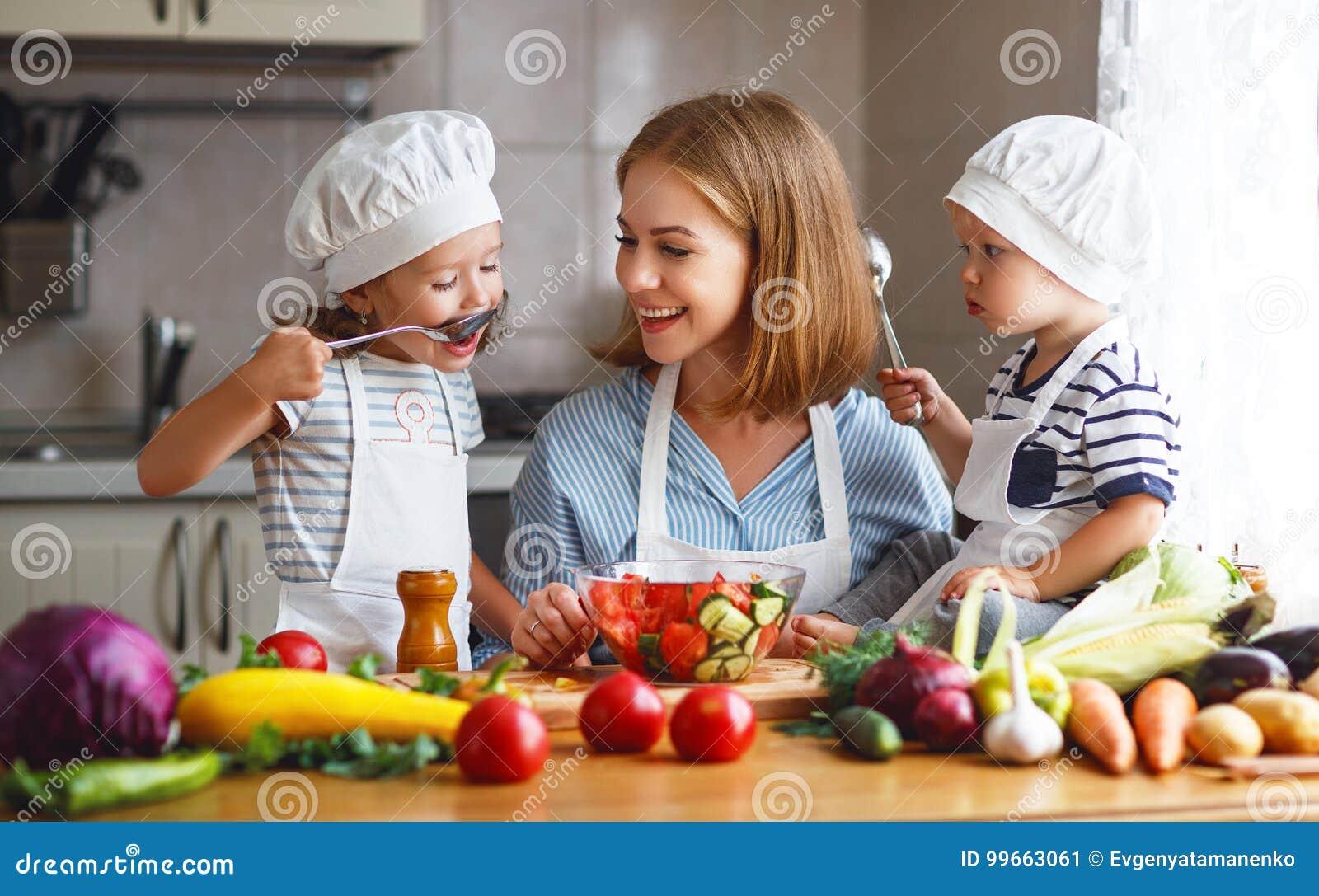 äta som är sunt Den lyckliga familjmodern och barn förbereder grönsaksallad