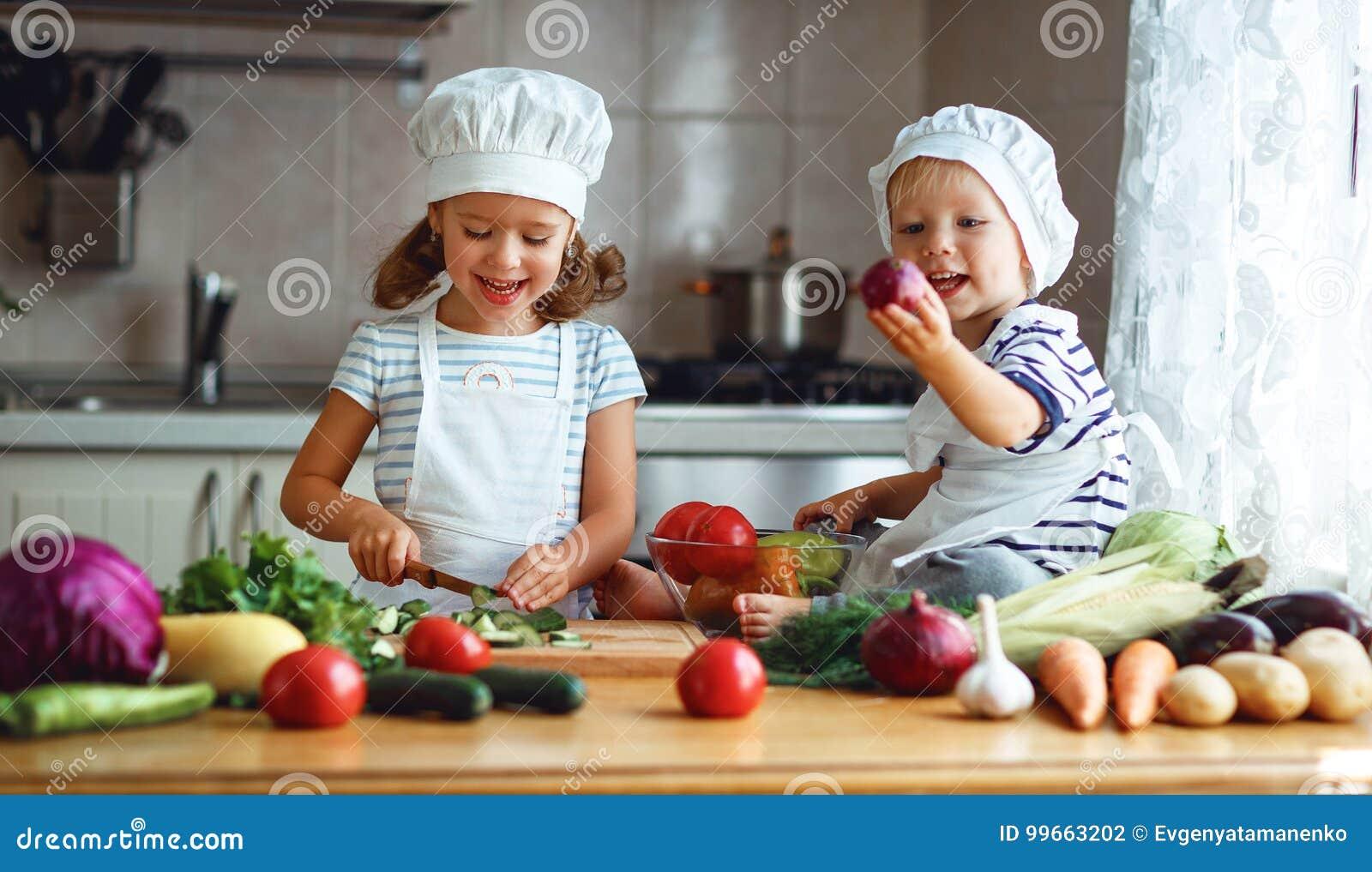 äta som är sunt Lyckliga barn förbereder grönsaksallad i kitc