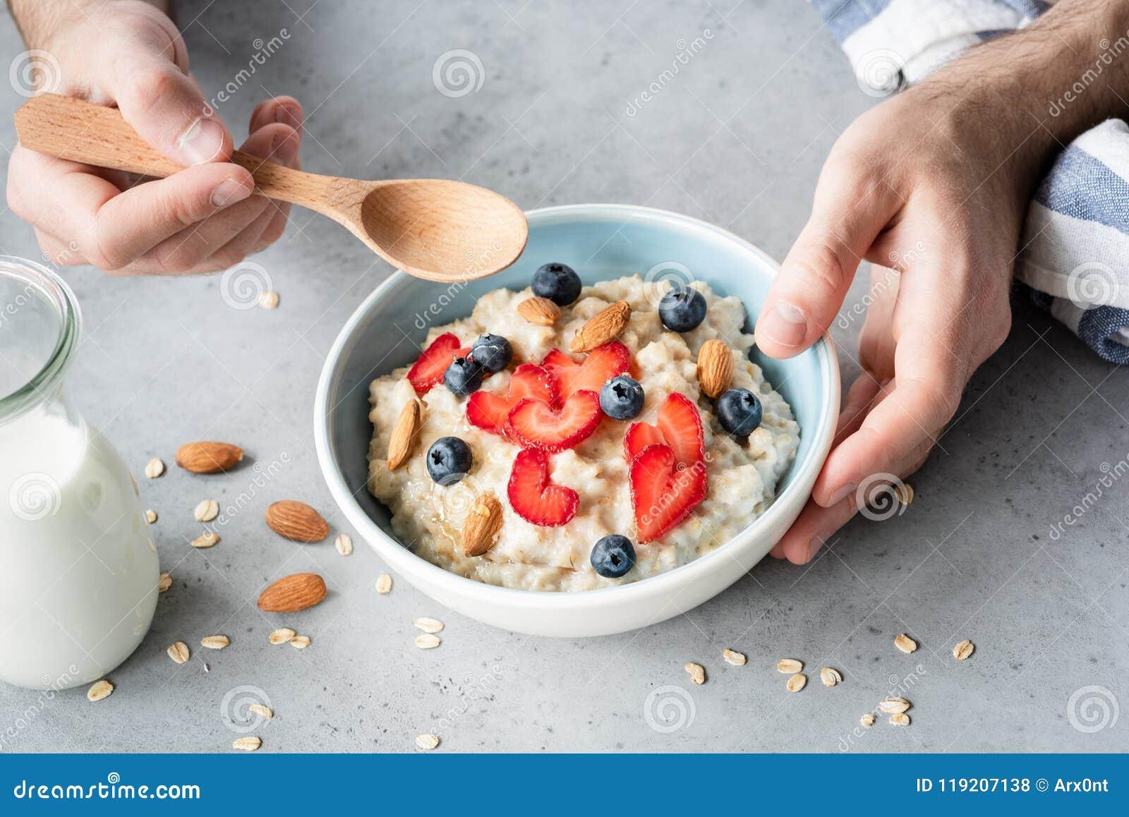 Äta sund frukosthavremjölhavregröt med nya bär och muttrar