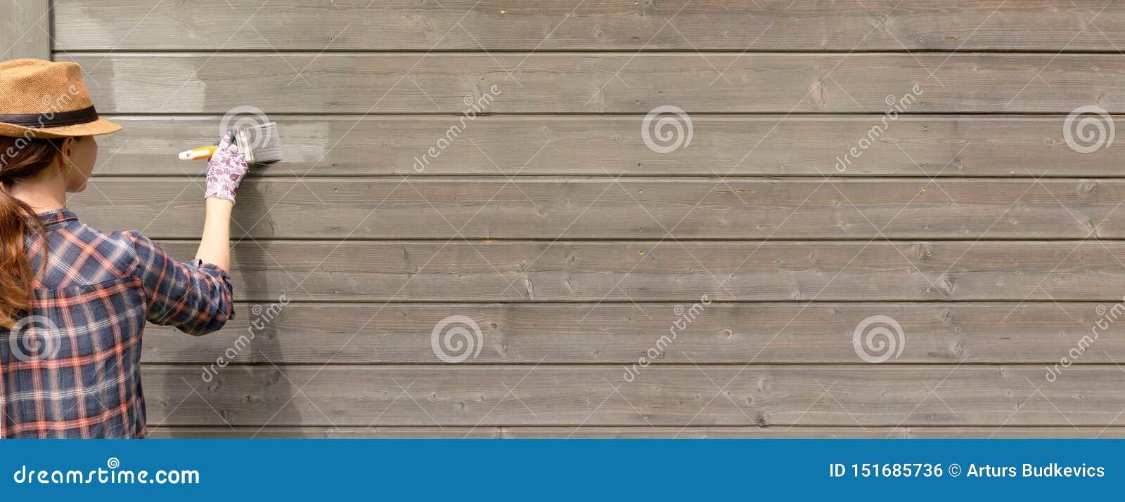 Äußere Wand des Arbeitnehmerin-Malereiholzhauses mit Malerpinsel und hölzerner schützender Farbe