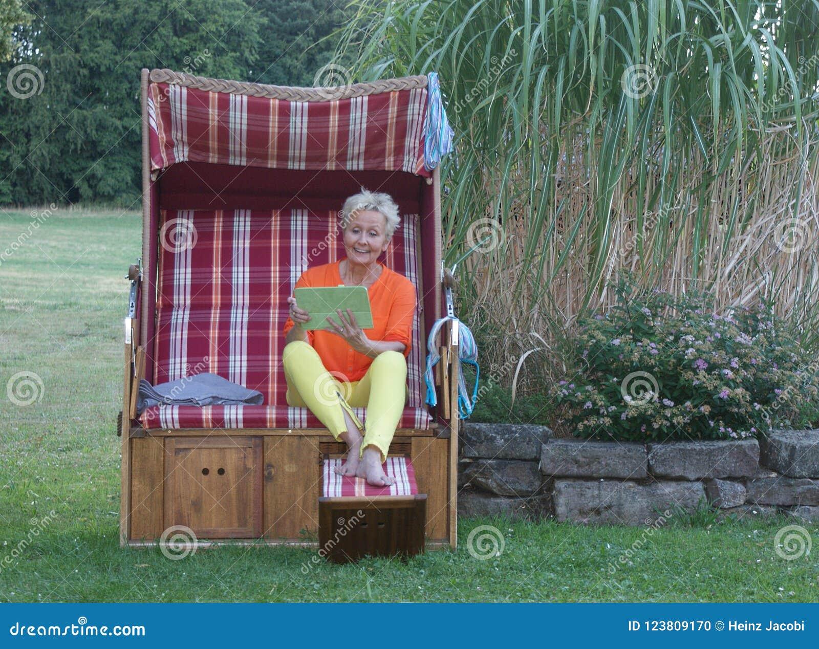 Även i en taklagd vide- strandstol, är den attraktiva kvinnan med minnestavlan alltid aktuell