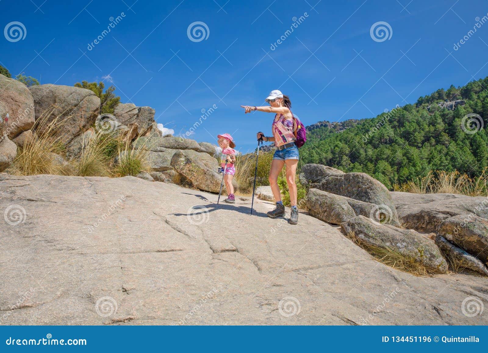 Äventyrliga kvinna och litet barn peka rutten i den Camorza klyftan nära Madrid