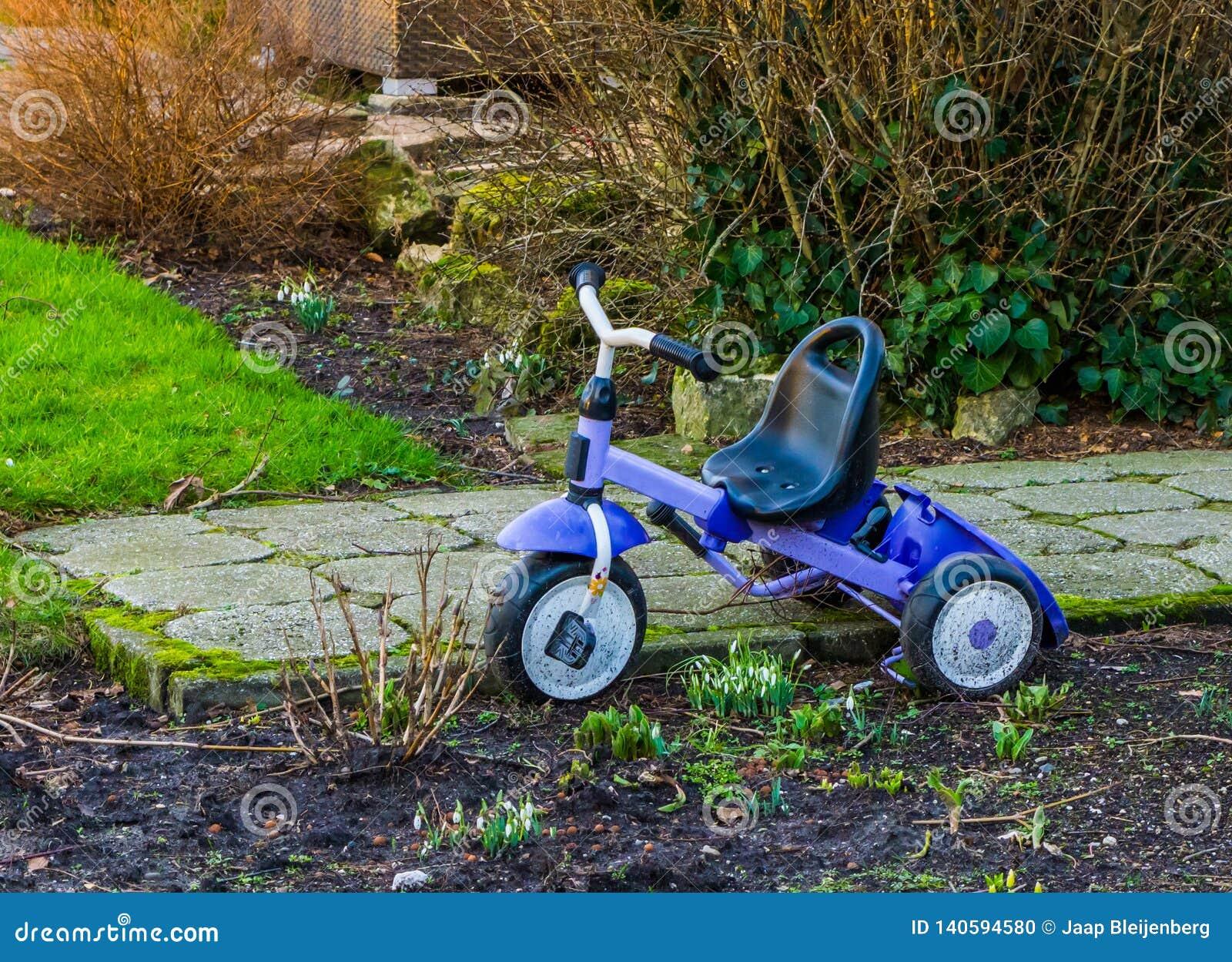 停放的三轮车在庭院里,儿童玩具,普遍的孩子玩具