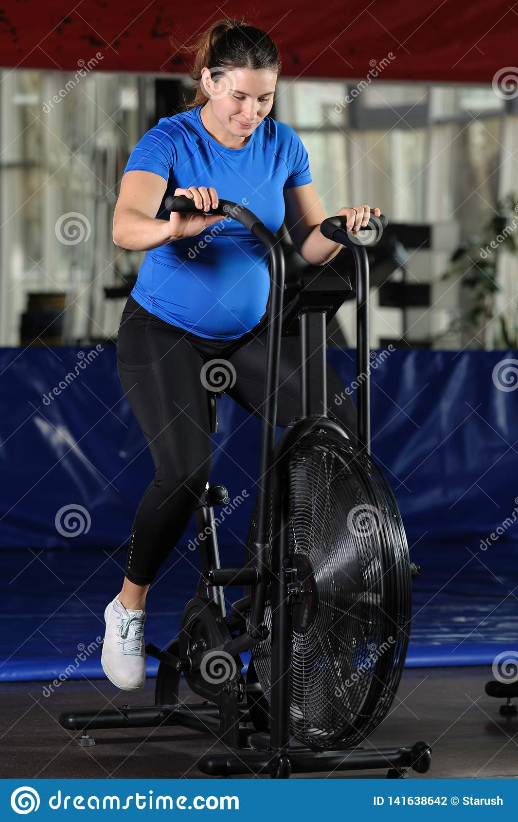 做强烈的锻炼的孕妇在健身房空气自行车