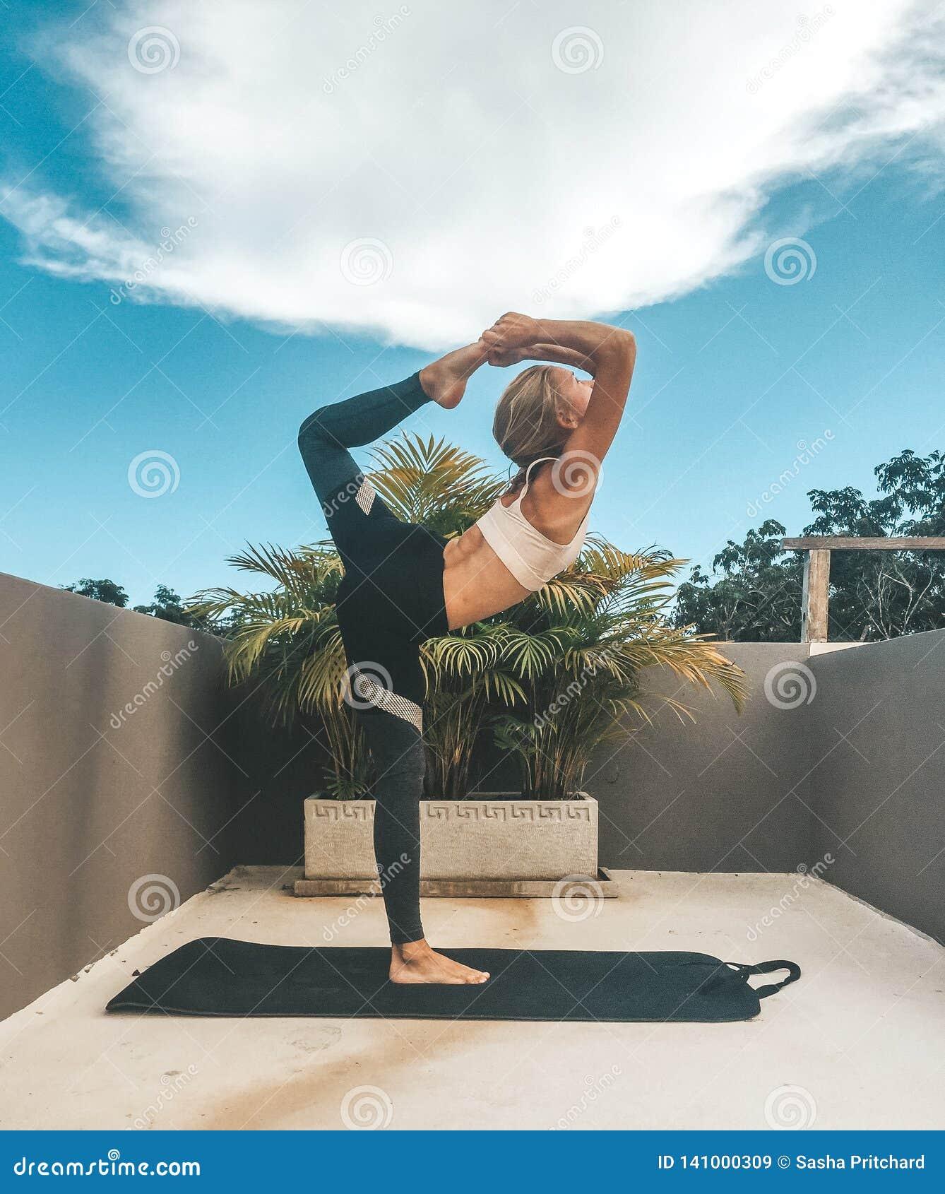 做瑜伽在屋顶的妇女舞蹈家姿势