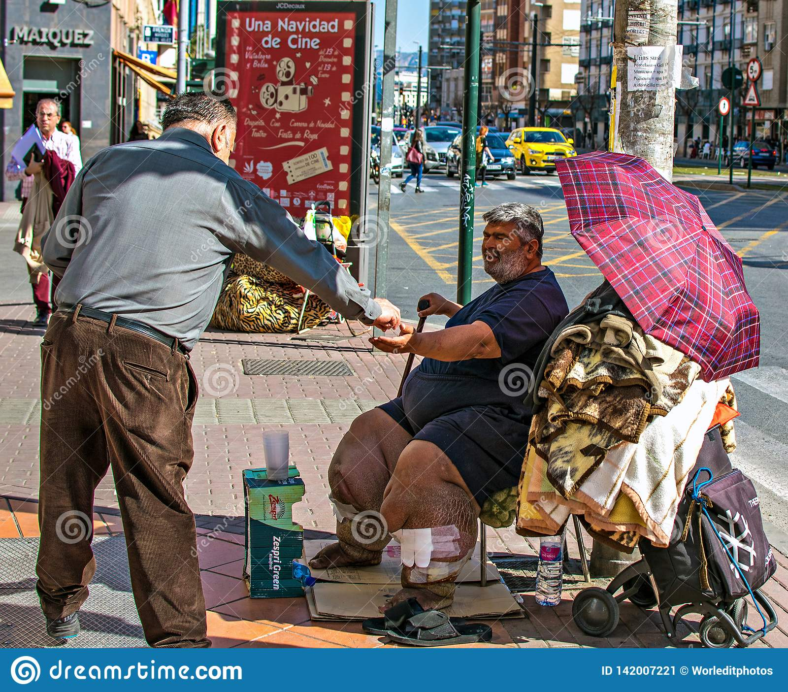 可怜的不健康的人乞求为在穆尔西亚,西班牙街道的施舍  人给贫寒捐钱