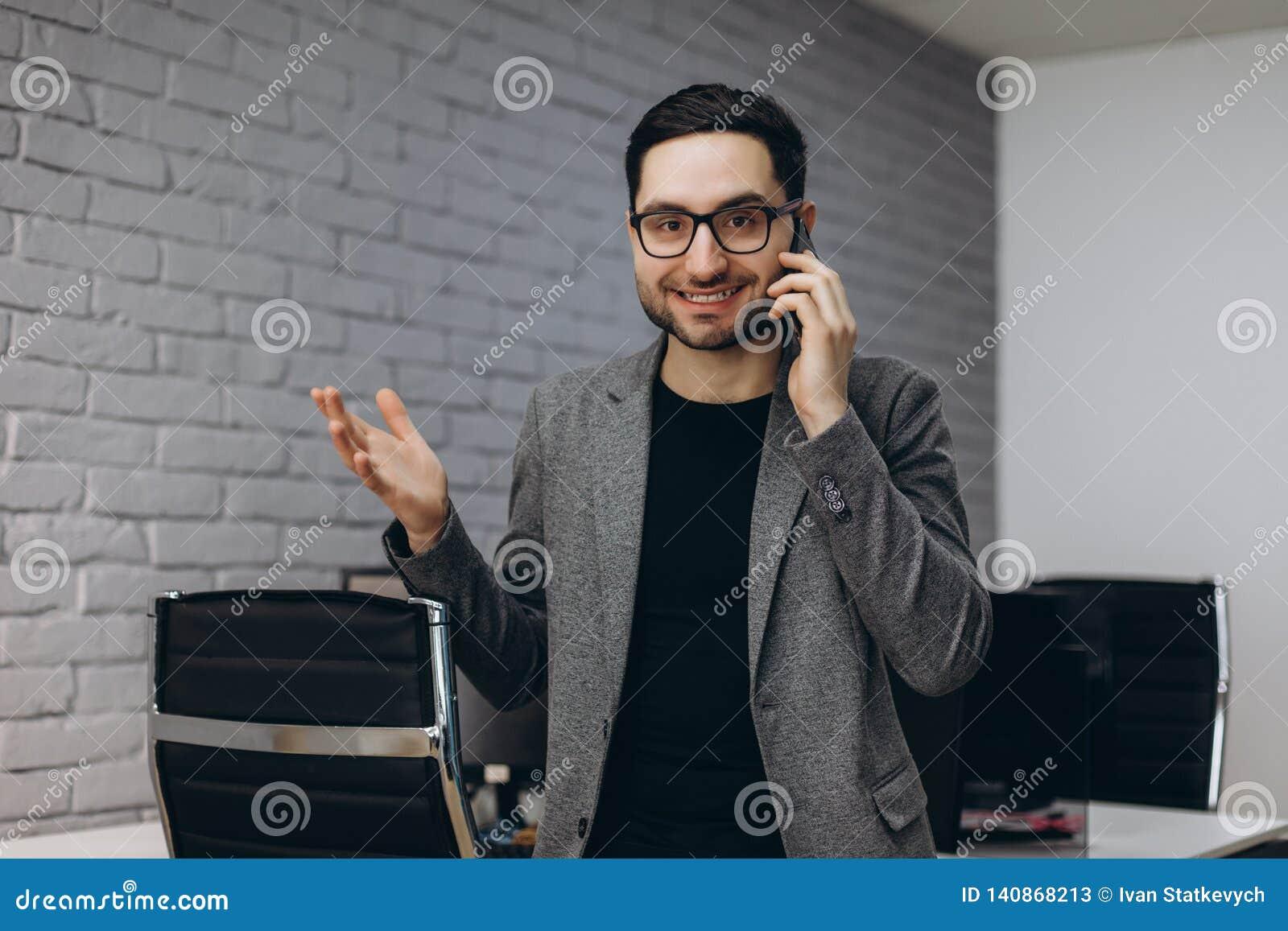 可爱的英俊的年轻深色的有胡子的微笑的行政工作者人在事务驻地职场,谈话电话的
