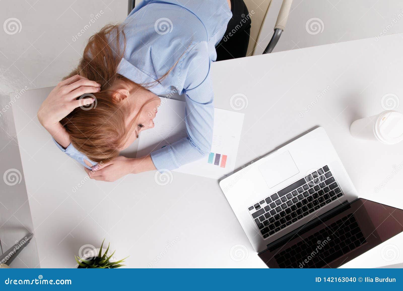 坐在她的工作场所的年轻女勤杂工感到坏 妇女有头疼