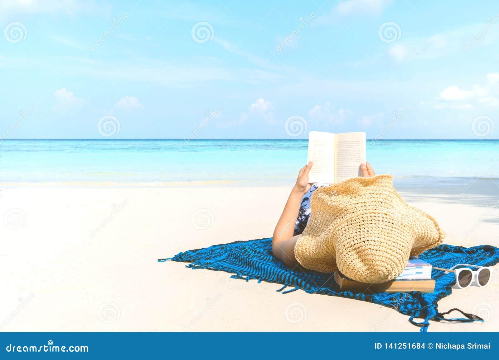 夏天海滩读书的假日妇女在海滩及时时间