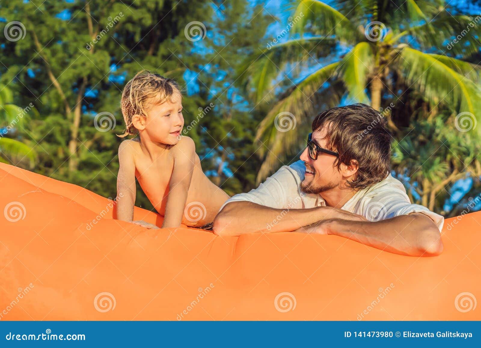 夏天父亲和儿子生活方式画象坐在海滩的橙色可膨胀的沙发热带海岛