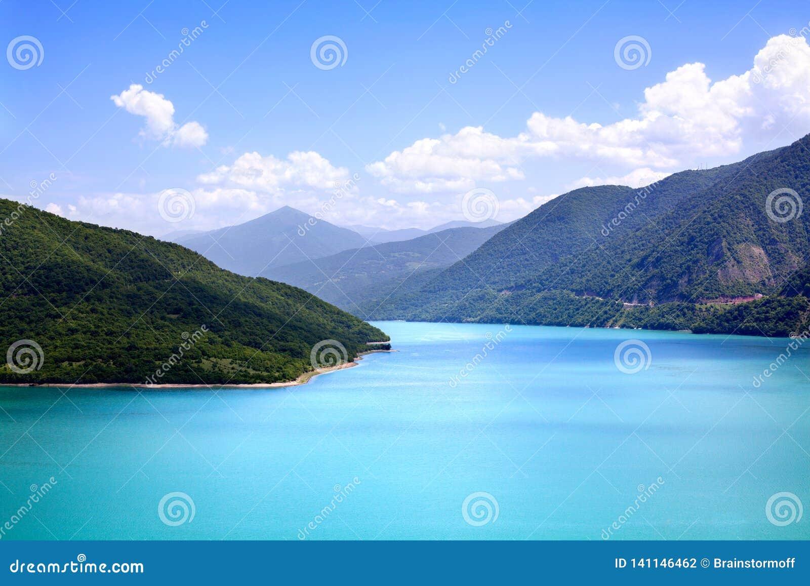 天蓝色的水在绿色山天空蔚蓝白色云彩背景中的一个蓝色盐水湖