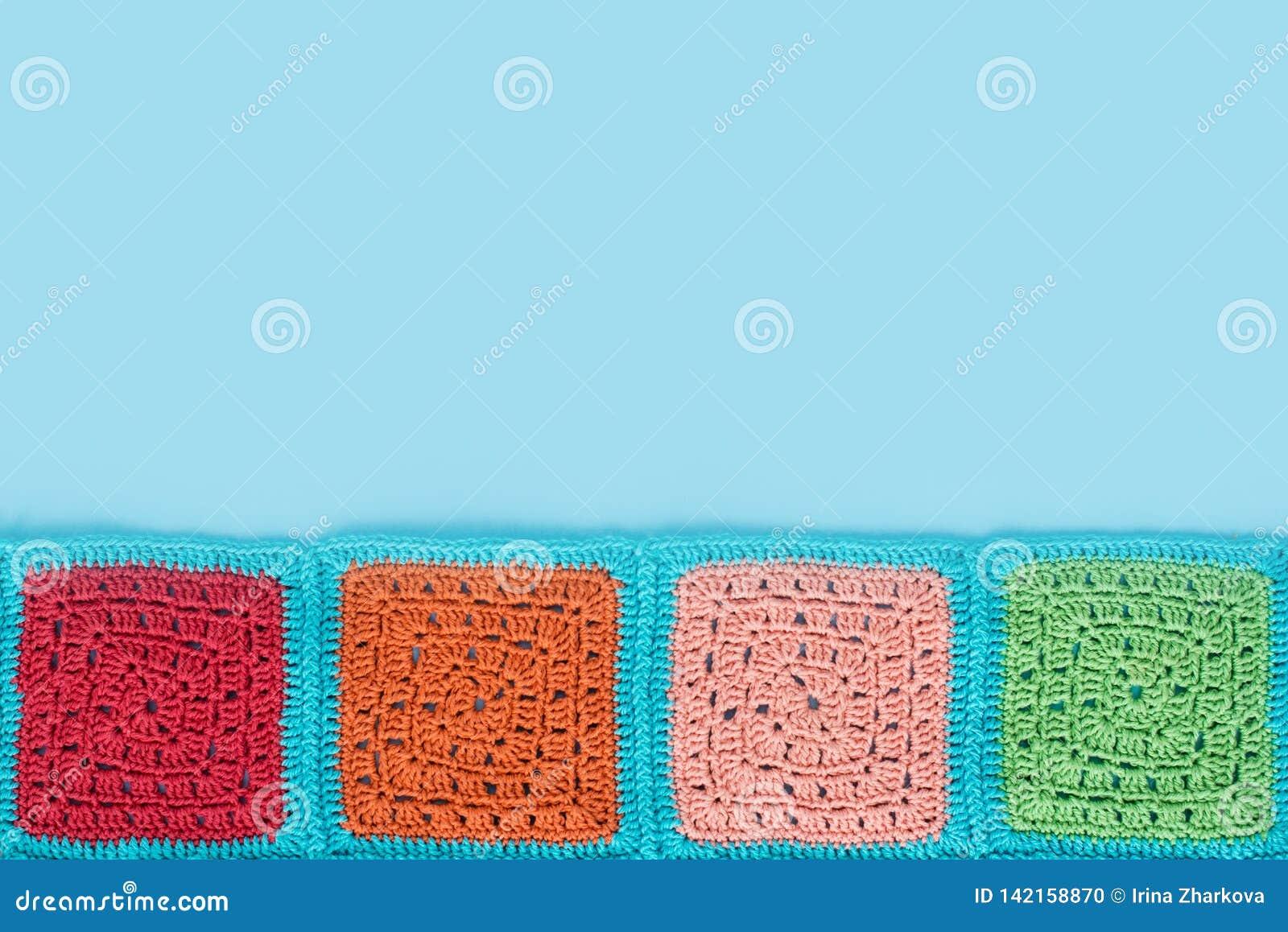 多彩多姿的正方形被钩编编织物的鞋带桌布在蓝色背景,顶视图,文本的,自然羊毛地方装饰