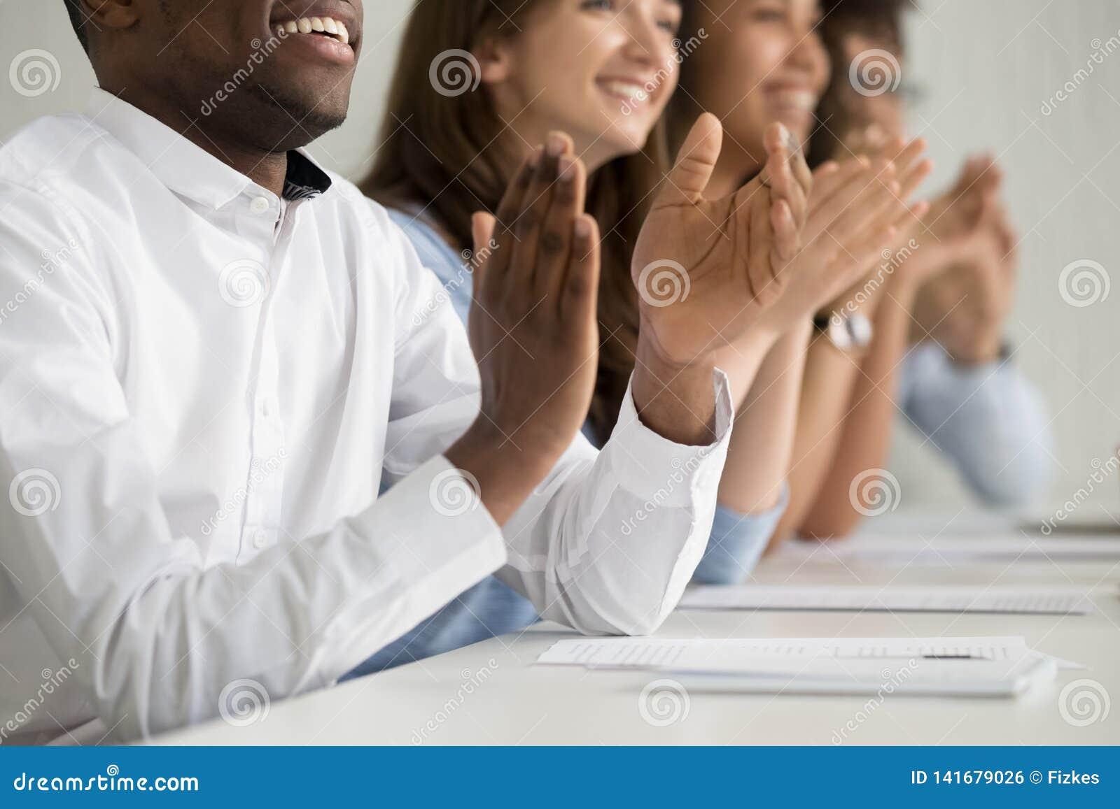 多种族企业观众人民赞许的坐在会议桌,特写镜头上