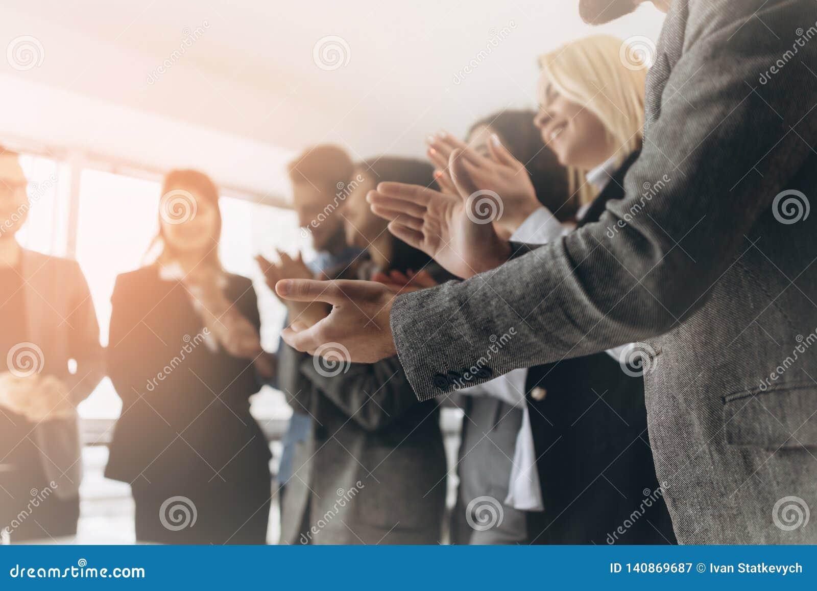 多种族小组祝贺他们的上司的商人拍的手-商业公司队,在a以后的起立欢呼