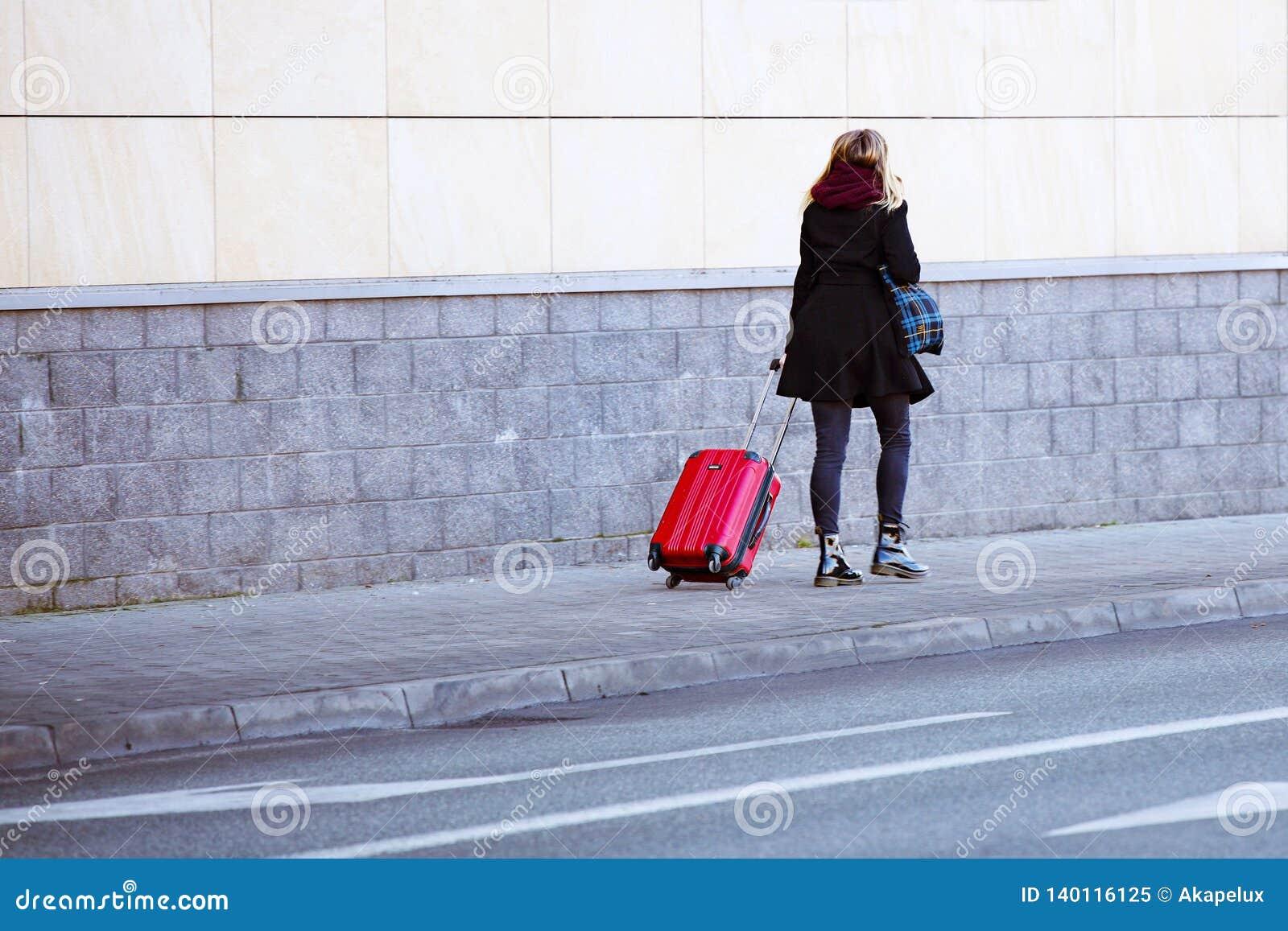 女孩在有一红色旅行包的边路走在轮子 一个现代时髦的手提箱的行李年轻游人 旅客是