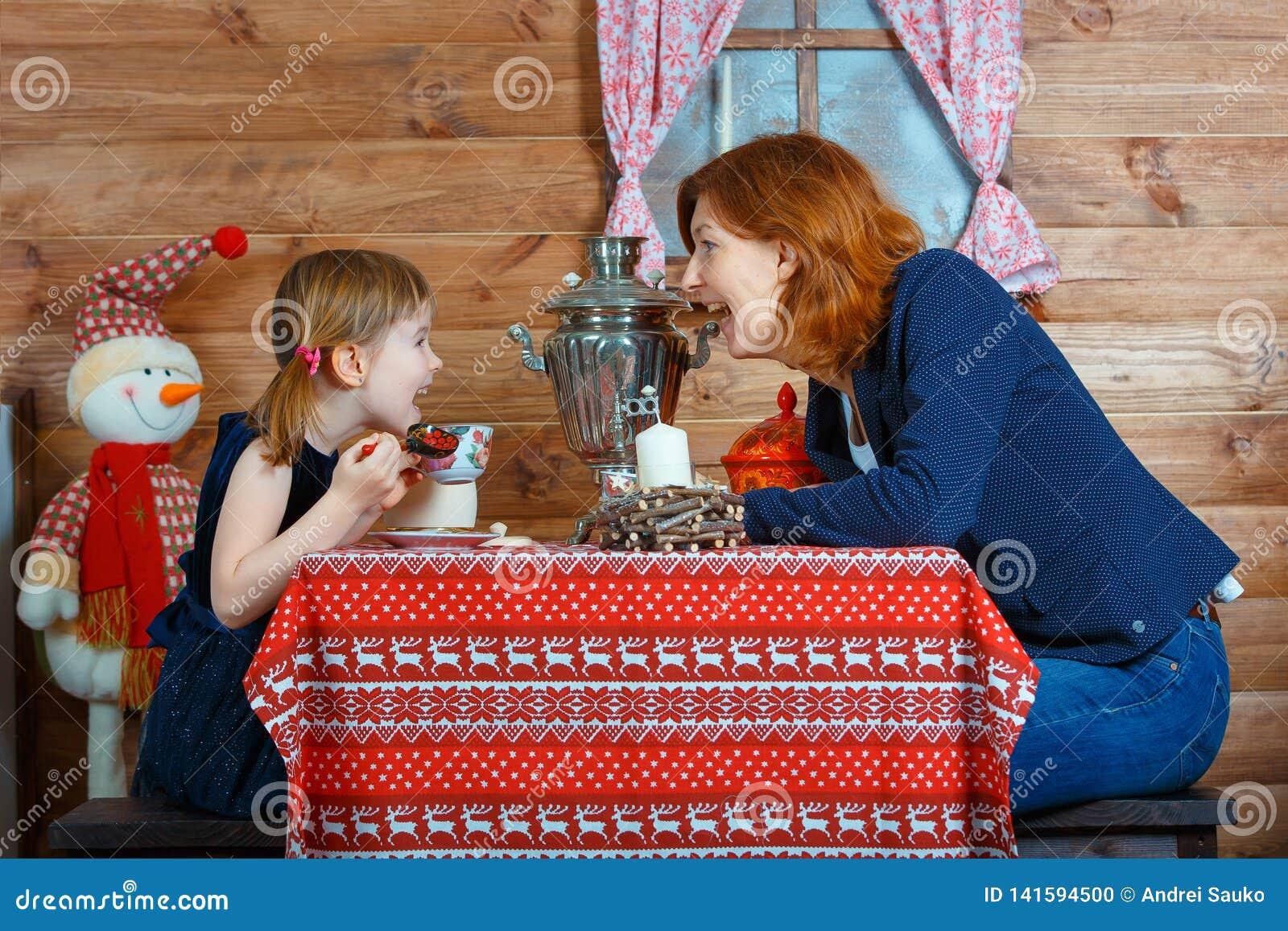 妈妈和女儿从俄国式茶炊和谈话的饮料茶