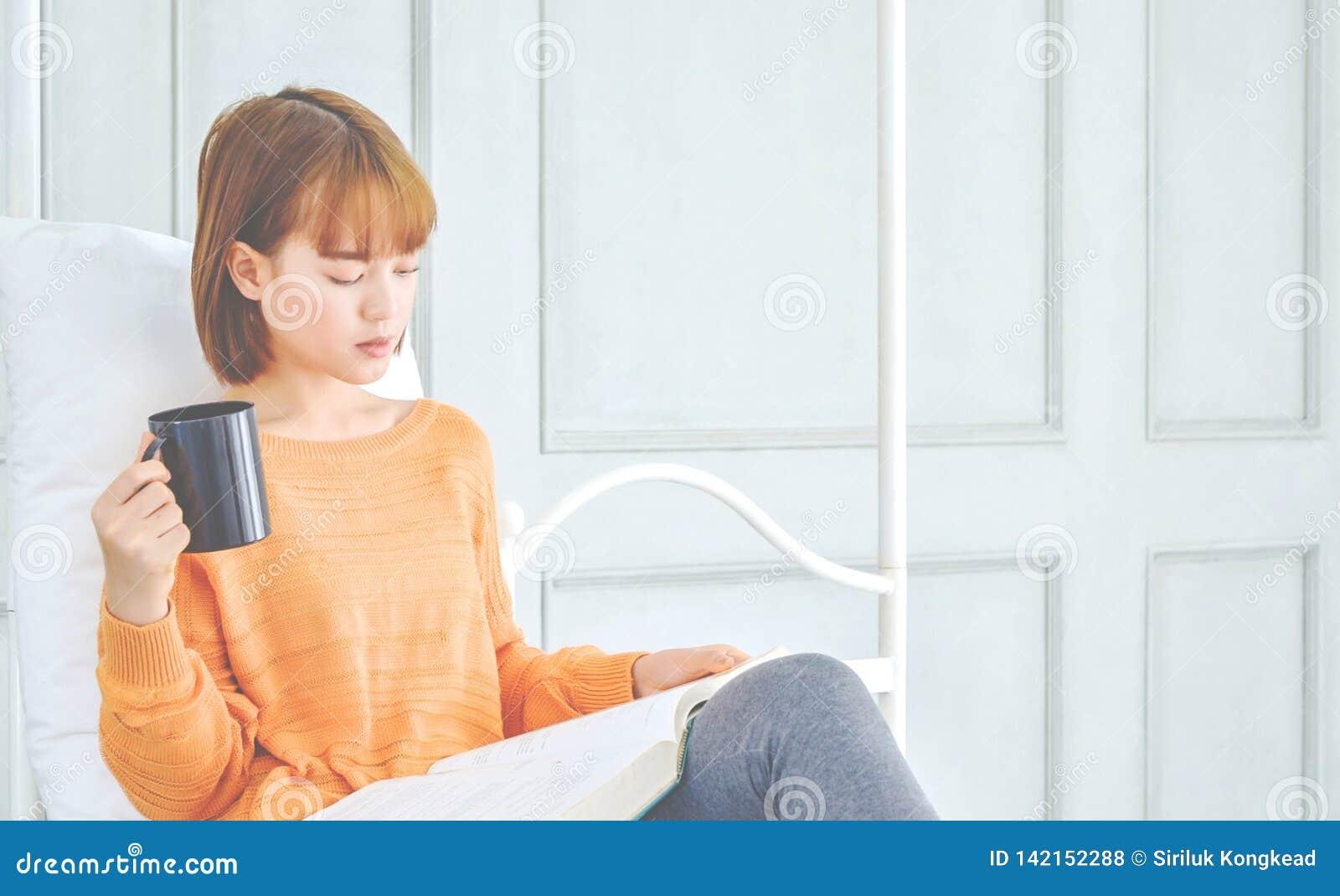 妇女读拿着一块黑玻璃的一本书