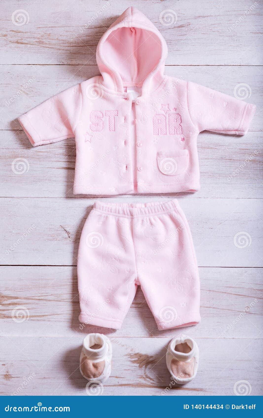 婴孩衣裳和辅助部件在白色木背景桌,桃红色儿童新出生的时装集合上女孩的,现代孩子婴儿