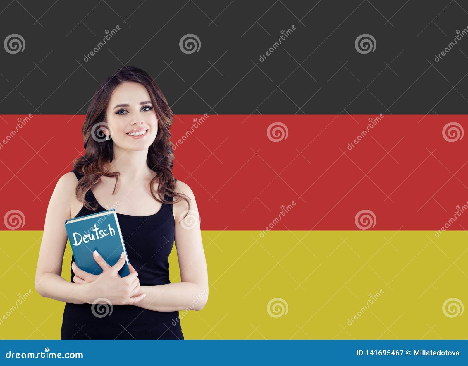 学会德语 拿着phrasebook的可爱的年轻女人反对德国旗子背景