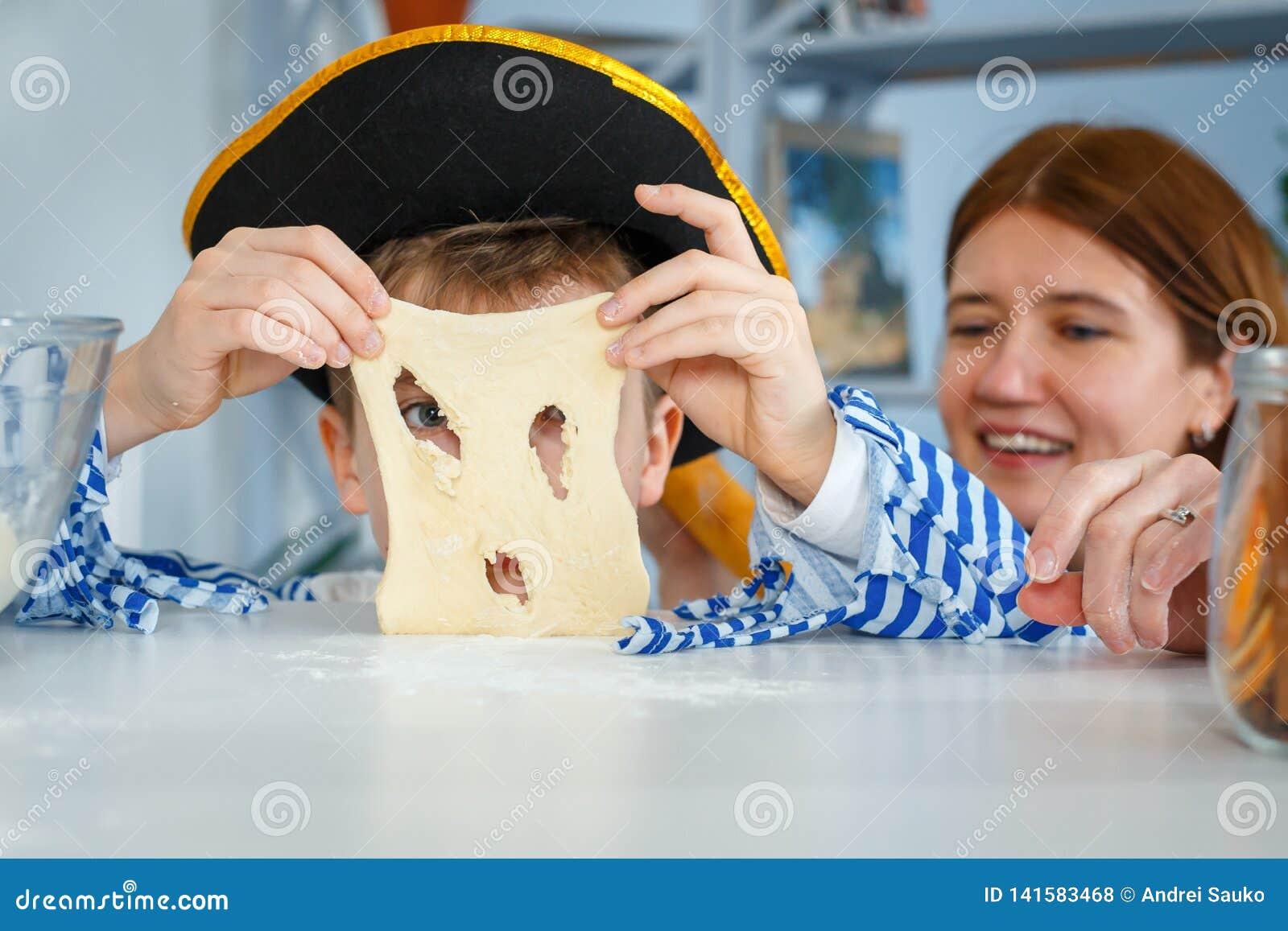 家庭一起烹调 妈妈和儿子揉面团用面粉 在厨房里准备面团