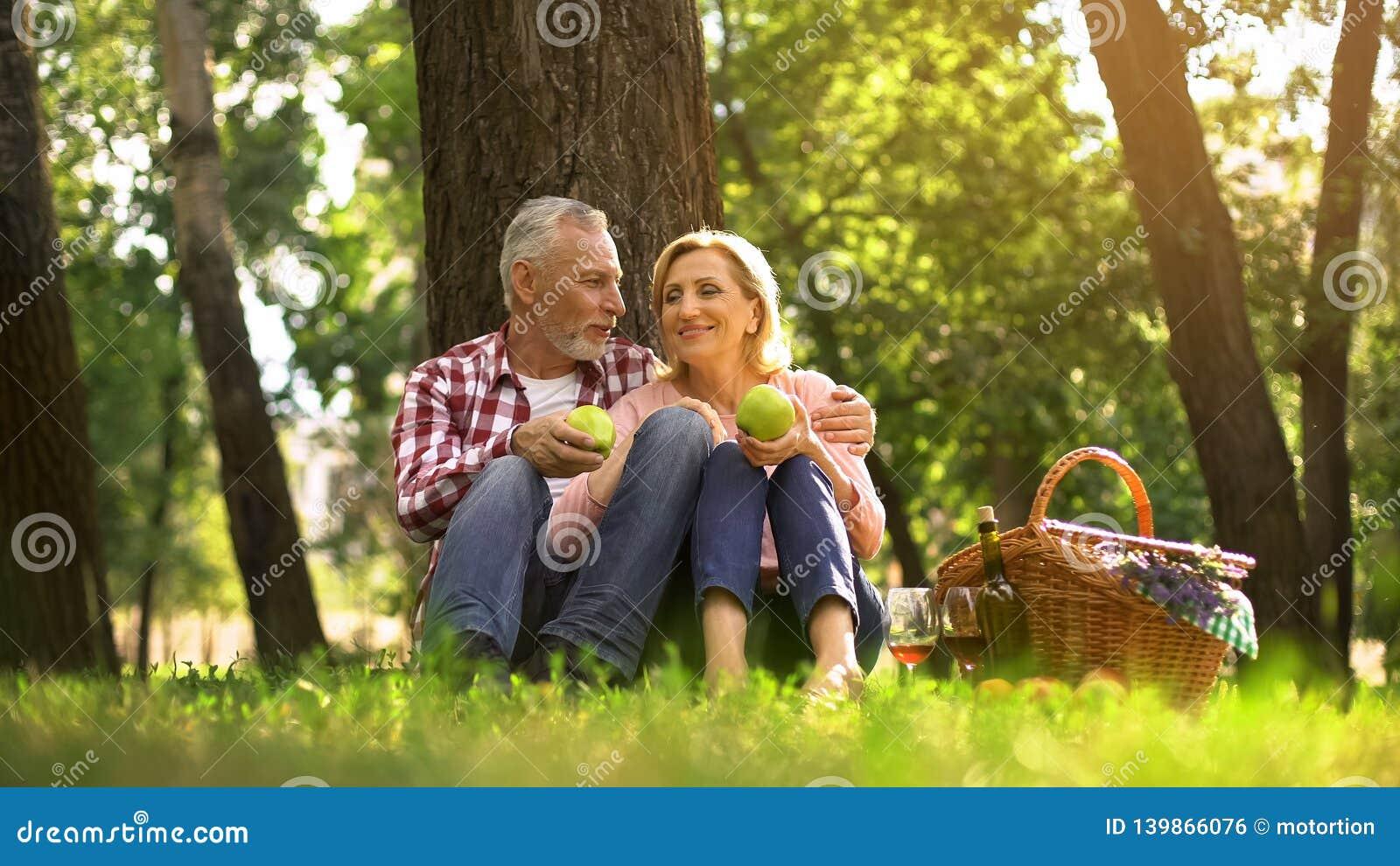 家庭周末,坐在公园和吃绿色苹果,野餐的退休的夫妇
