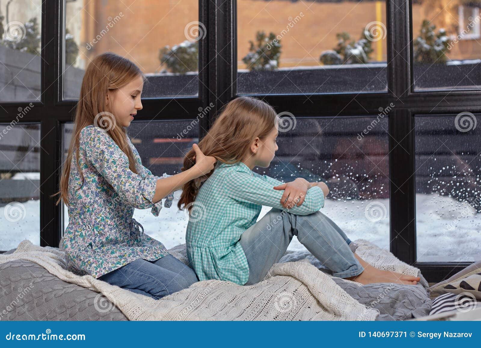 安静两个逗人喜爱的妹的图象坐在和平的窗台和