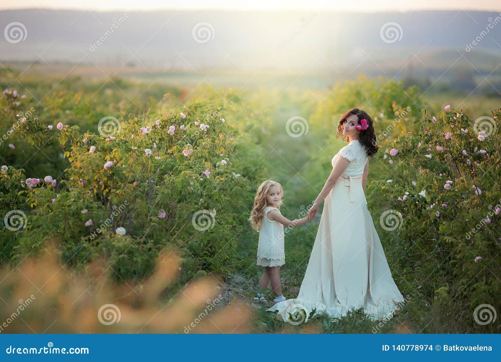 幸福家庭:有她的走在a的麦子橙色领域的小逗人喜爱的女儿的一年轻美丽的孕妇