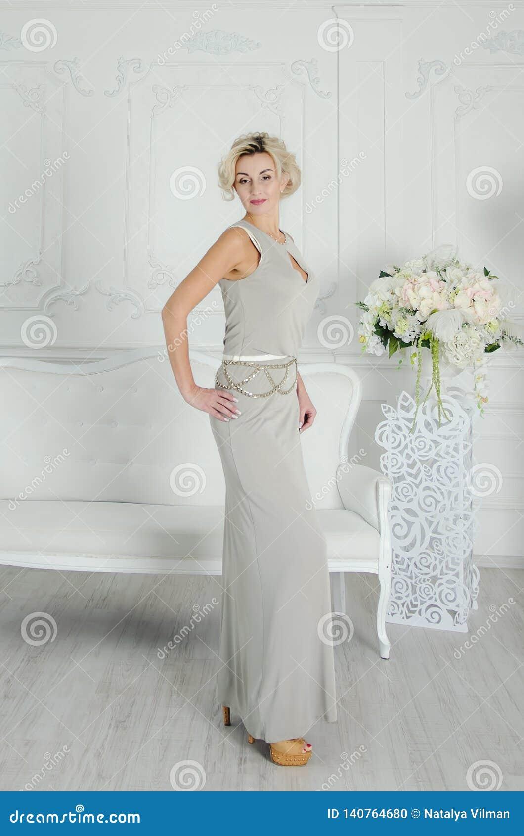 40年的花姑娘在一件长的晚礼服的 在淡色的别致的内部