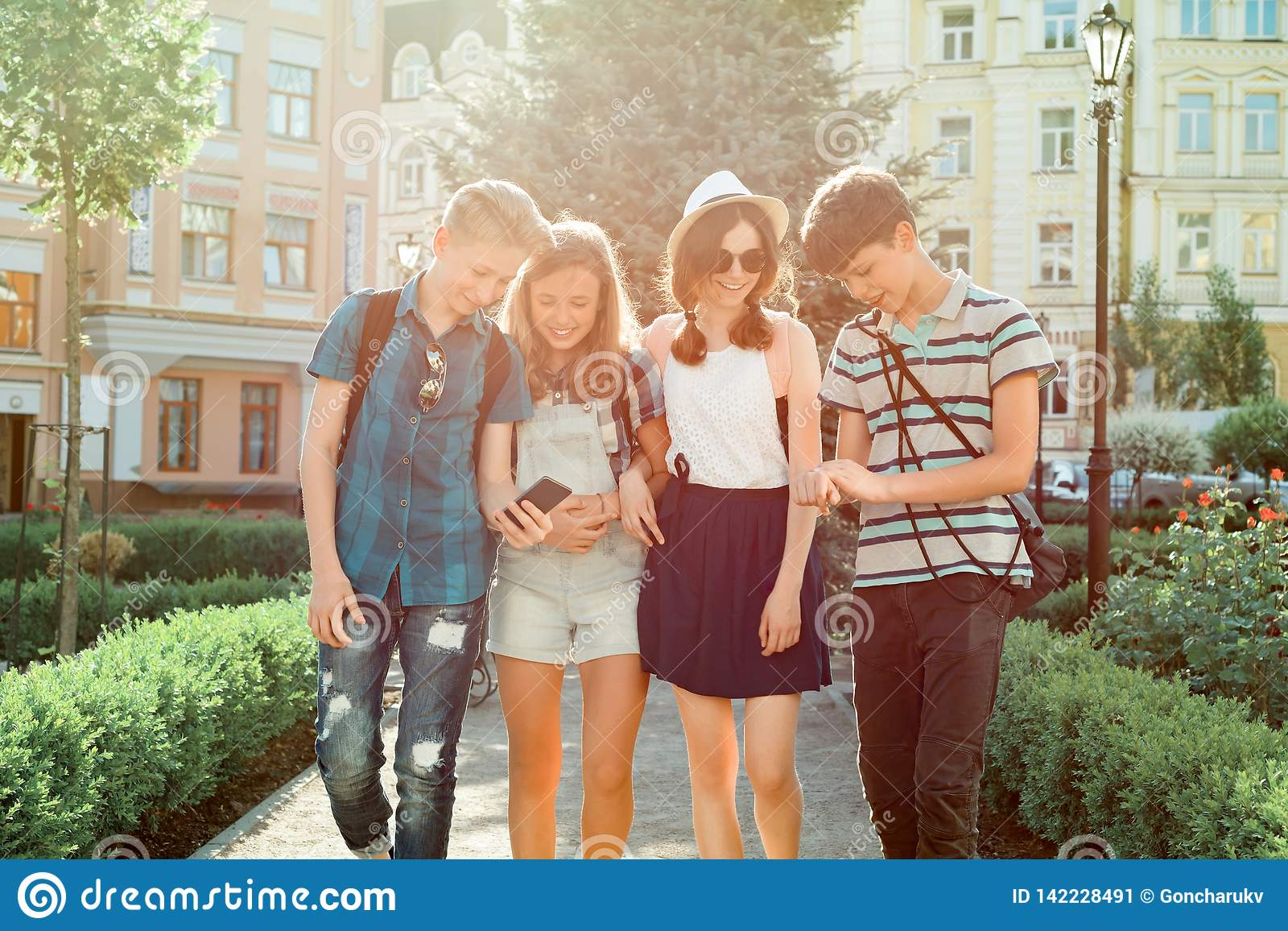年轻人走在城市,谈话一个小组的朋友的少年微笑获得乐趣在城市 友谊和人们