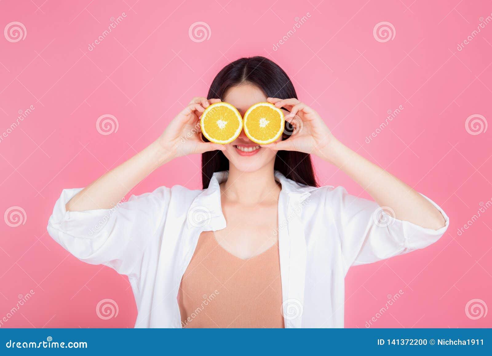 年轻亚裔妇女健康微笑的显示的桔子