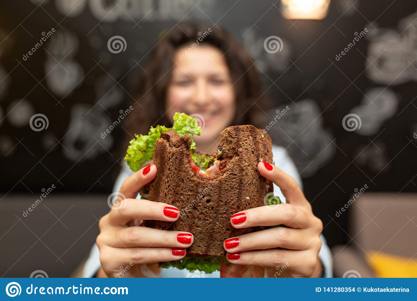 年轻女人举行被咬住的三明治特写镜头滑稽的被弄脏的protrait由她的两只手的 三明治在焦点 可能