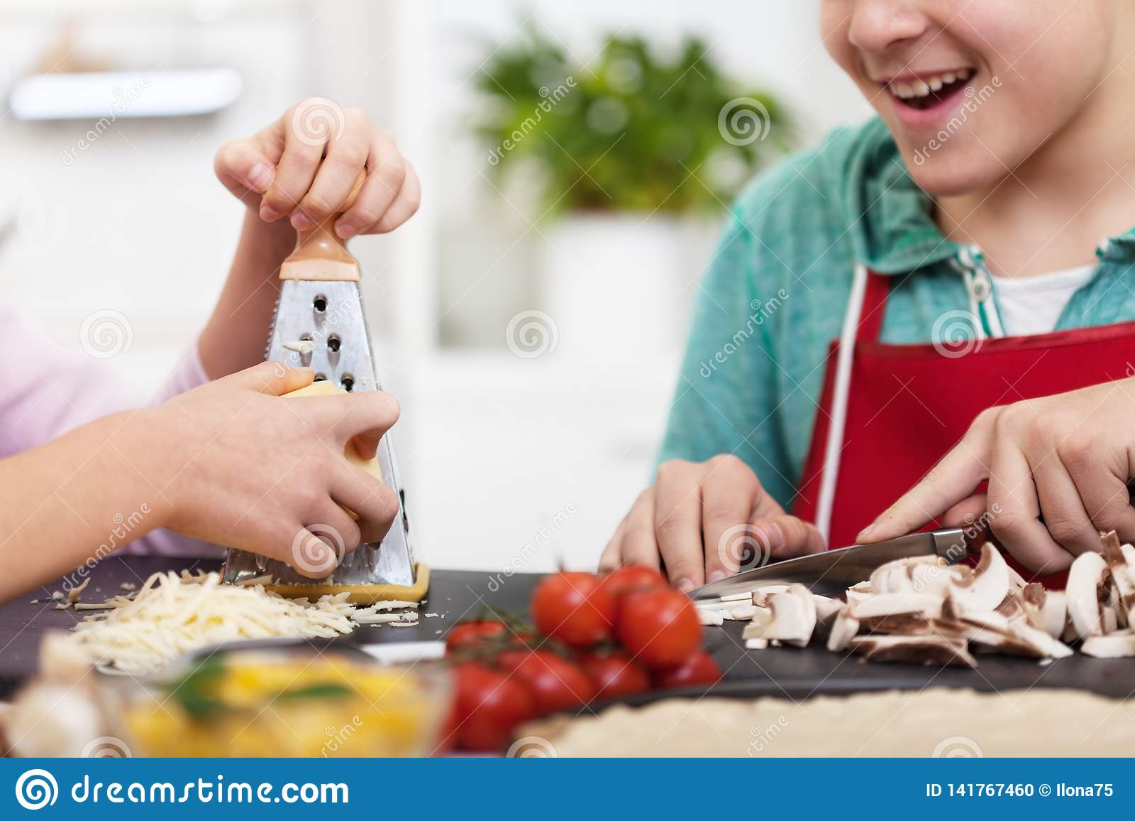 年轻少年手在接近的厨房里准备一比萨-