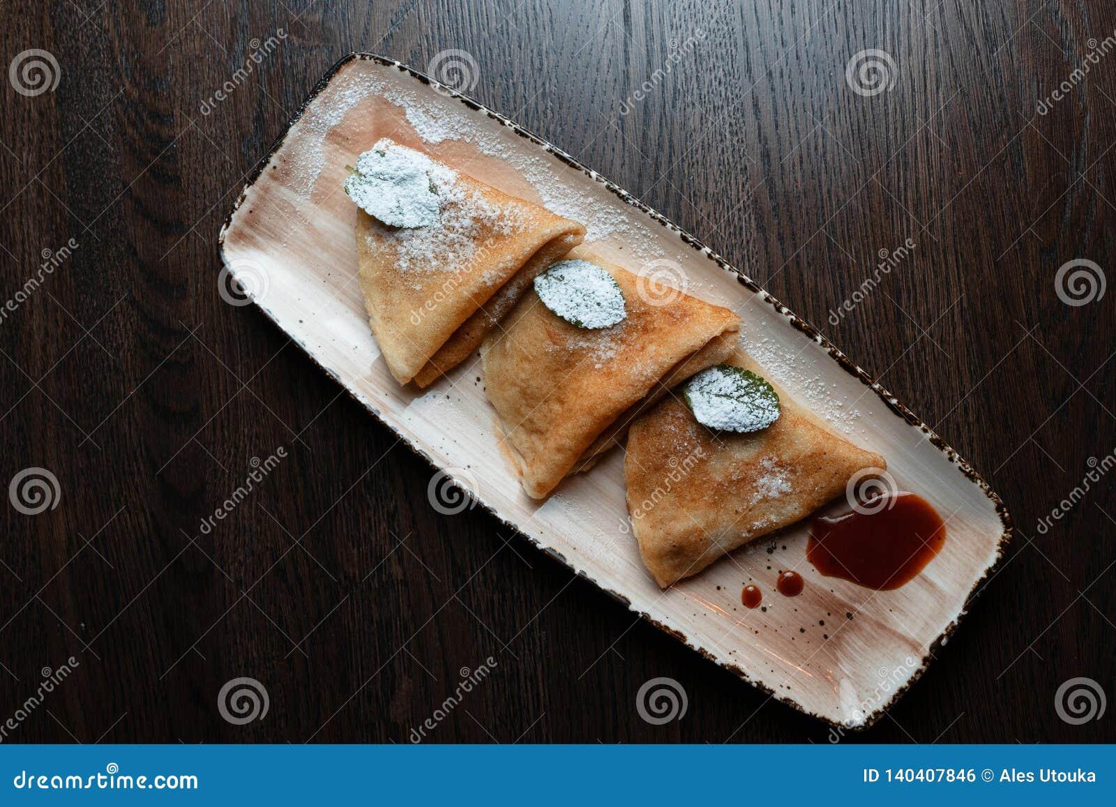 开胃金黄稀薄的薄煎饼用甜草莓酱装饰用在一块板材的糖粉在餐馆 可口点心