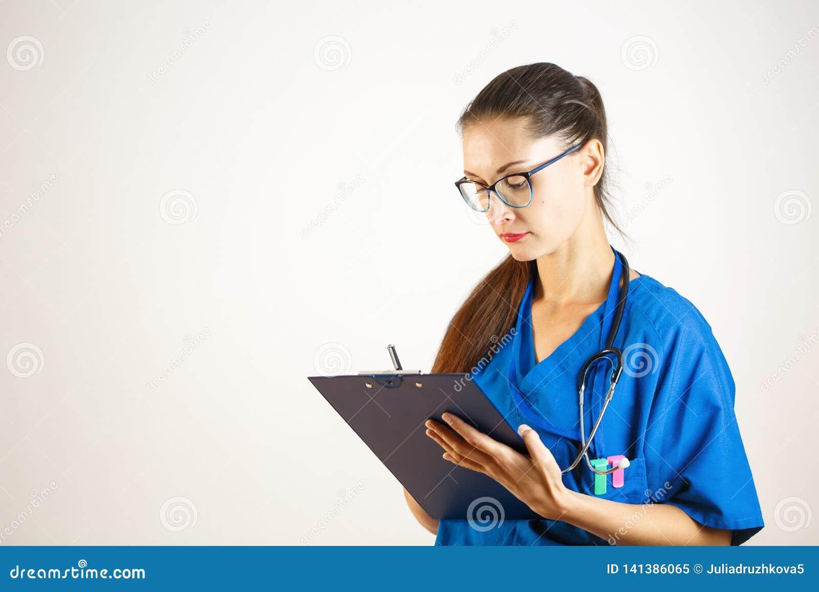 Żeńska lekarka w błękitnym kontuszu nagrywa dane w czasopiśmie, stetoskop jest na jej szyi Biały tło