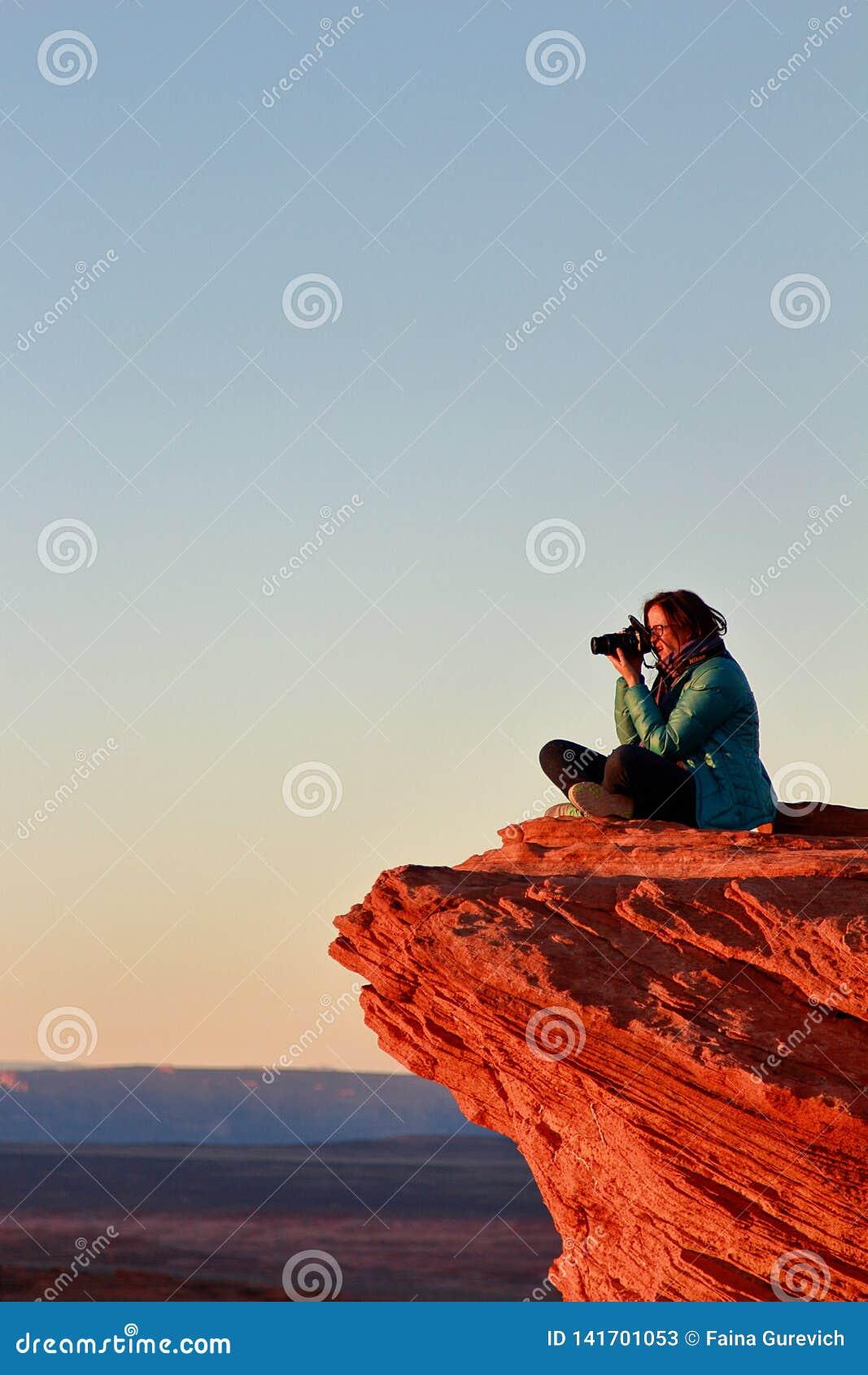 Żeński fotograf bierze obrazki z dużym kamery obsiadaniem na krawędzi falezy przy podkowa chyłem