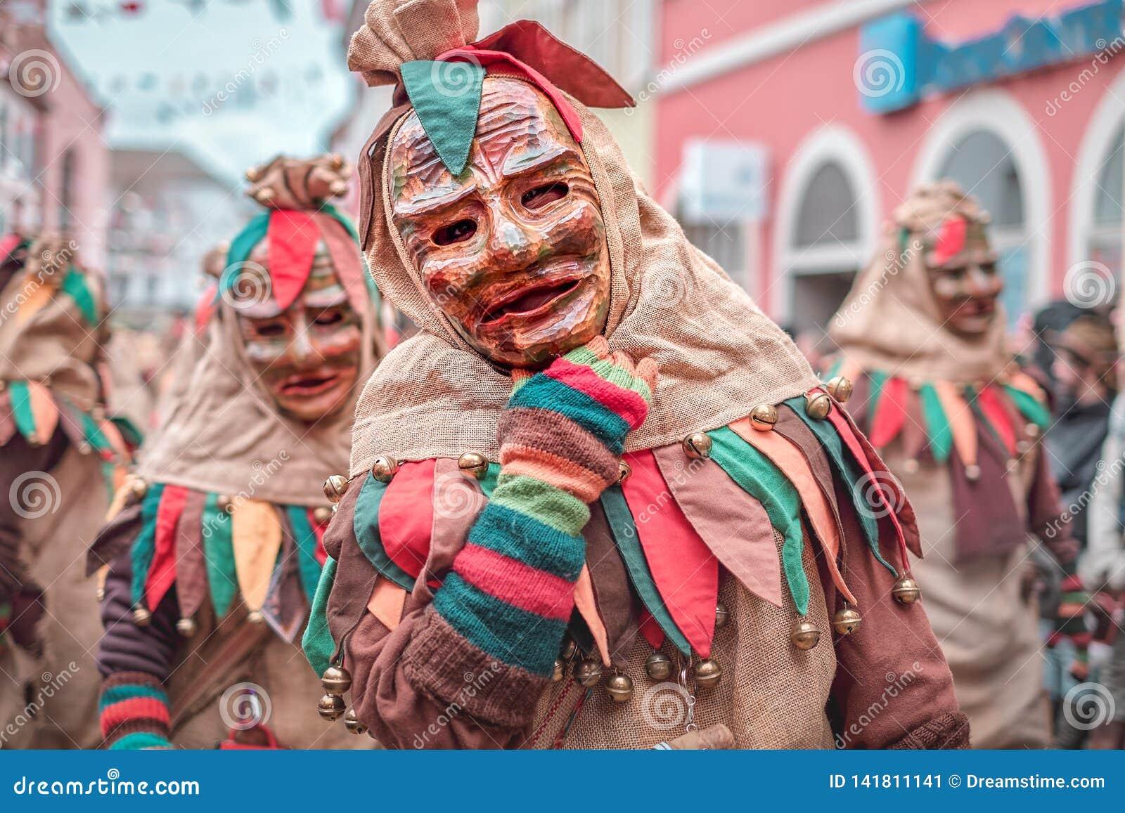 Życzliwa carnaval postać w brązie, zieleń, czerwony kontusz pokazuje ręka gest Karnawał w południowym Niemcy - Czarny las
