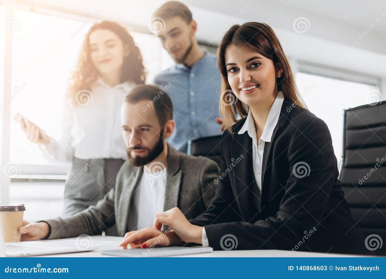 当她的同事在背景中时,工作可爱的年轻企业夫人看照相机并且微笑着